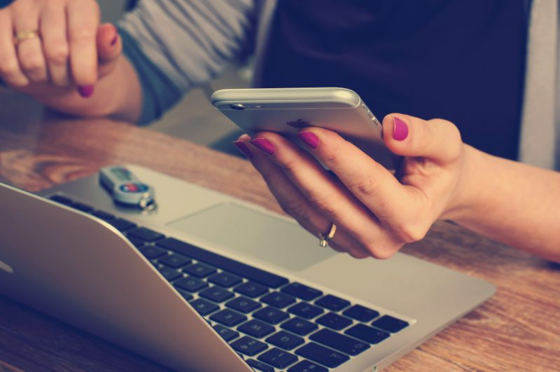 Eine Frau verwendet Ihr Smartphone vor dem Laptop