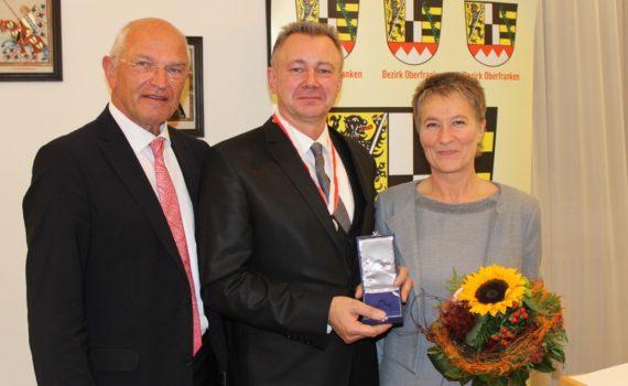 Bezirkstagspräsident Dr. Günther Denzler und Hans Thomann jr. mit seiner Frau Gabriele Thomann bei der Verleihung der Ehrenmedaille des Bezirks Oberfranken (Foto: Christian Porsch)